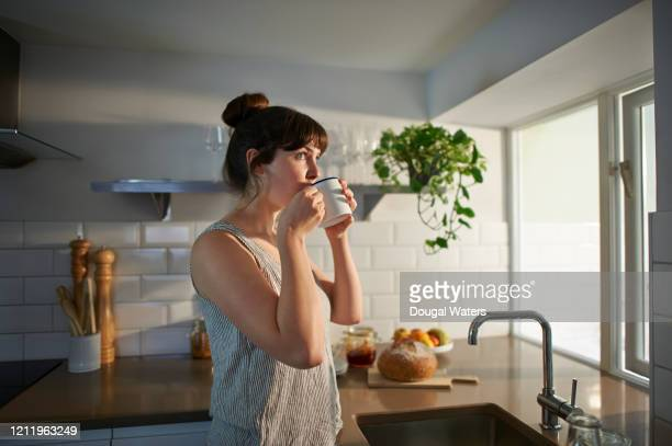 woman drinking from mug in zero waste kitchen. - serene people stock pictures, royalty-free photos & images