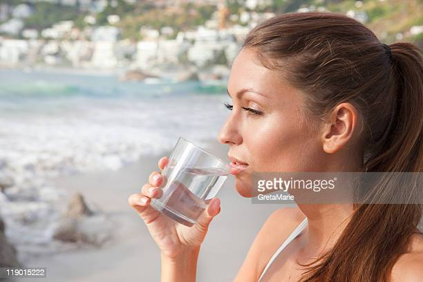 Woman drinking glass of water on beach