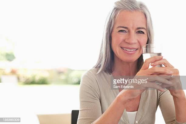 mujer vaso de agua - agua potable fotografías e imágenes de stock