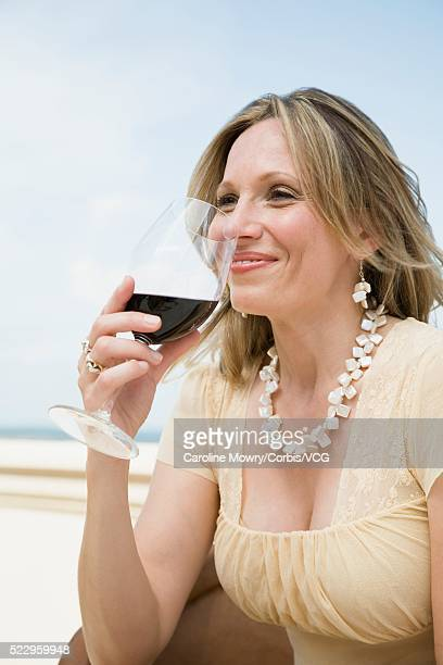 woman drinking glass of wine - candid cleavage stock pictures, royalty-free photos & images