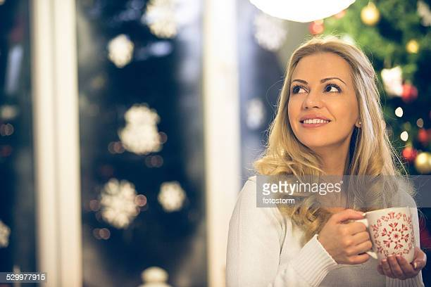 Woman drinking hot drink on Christmas eve
