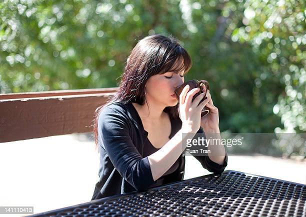 Woman drinking hot tea in cup at park