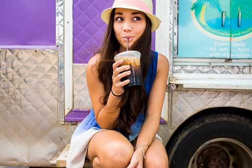 Woman drinking ice coffee near food cart - gettyimageskorea