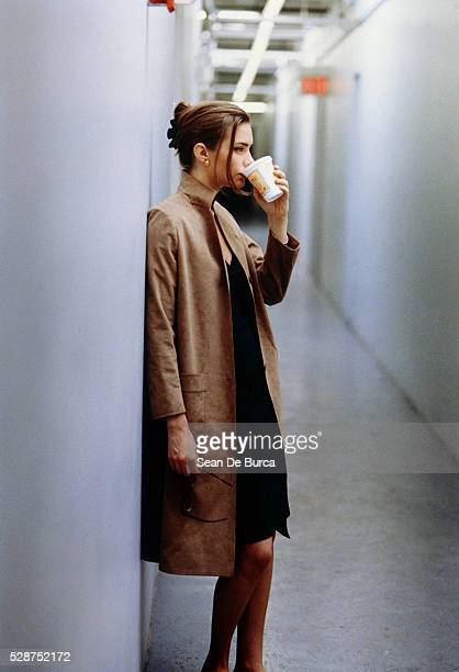 woman drinking in corridor - overcoat stock pictures, royalty-free photos & images