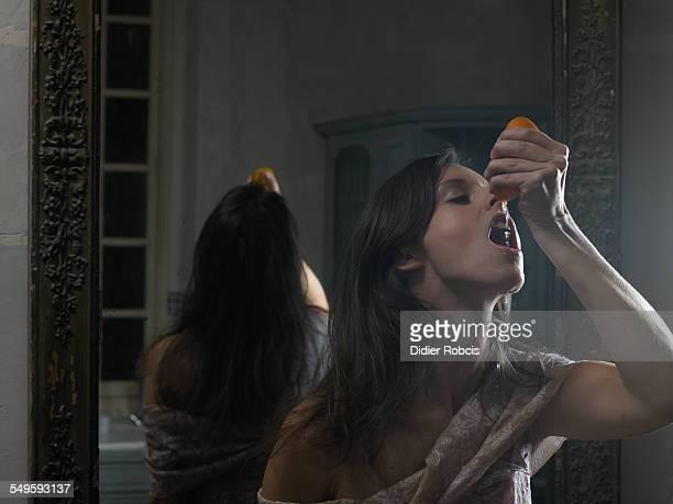Woman Drinking Juice of an Orange