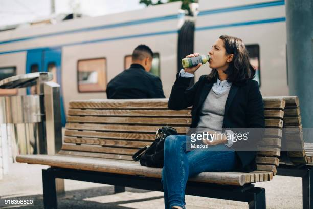 woman drinking juice while sitting on bench at platform by train - wachten stockfoto's en -beelden