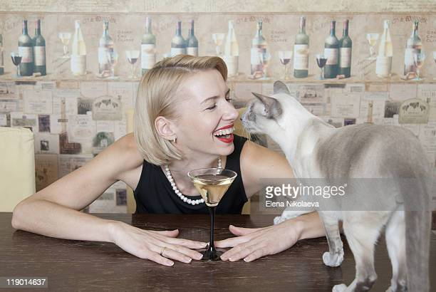 Woman drinking martini with cat