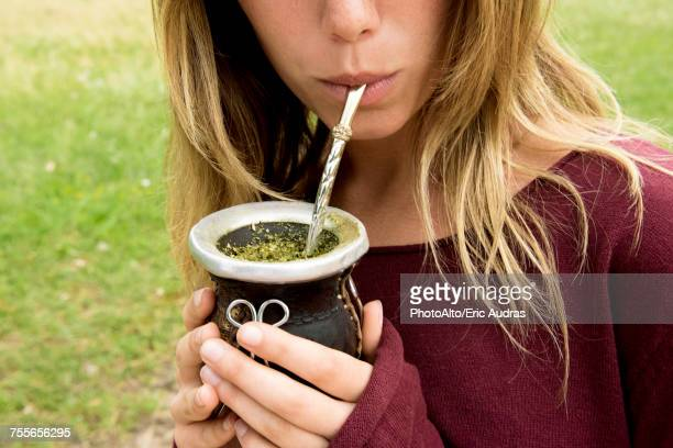 Woman drinking mate from gourd