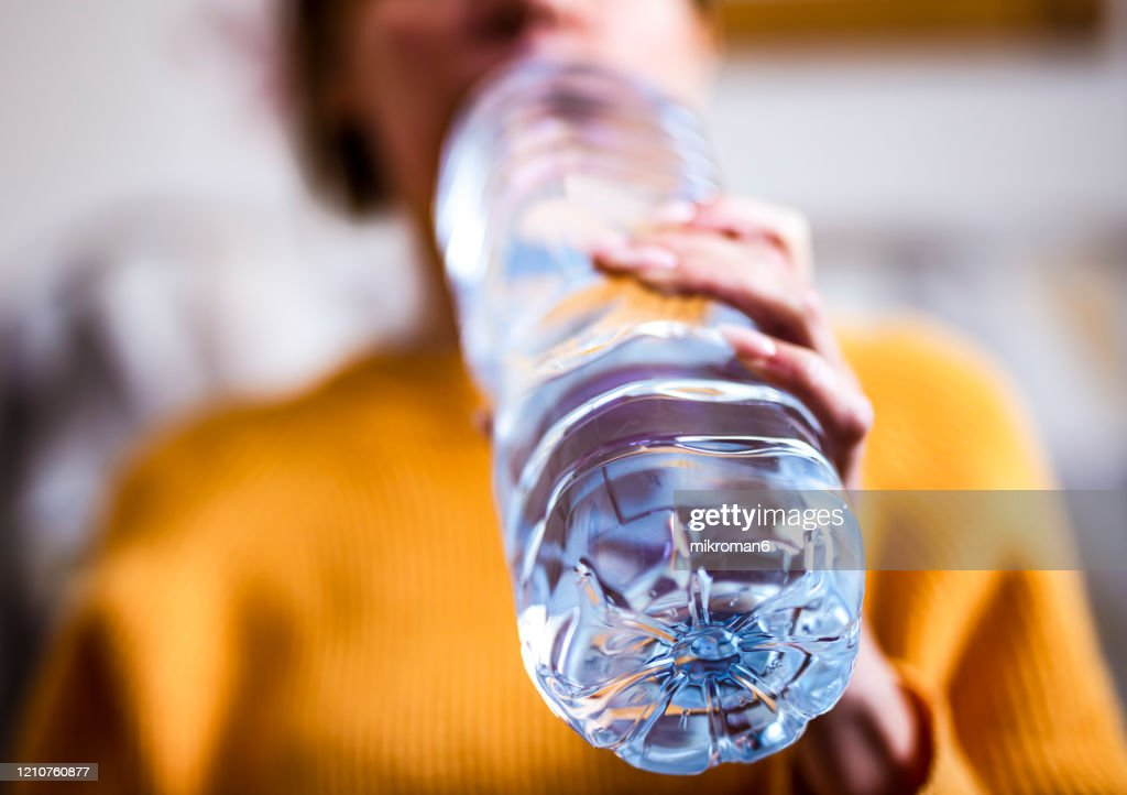 Woman drinking mineral water from the bottle : Stock Photo