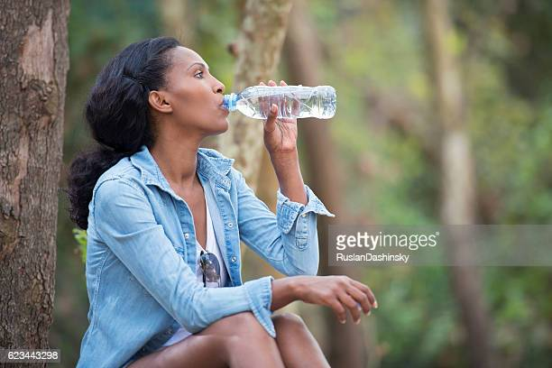 Woman drinking mineral water outdoors.