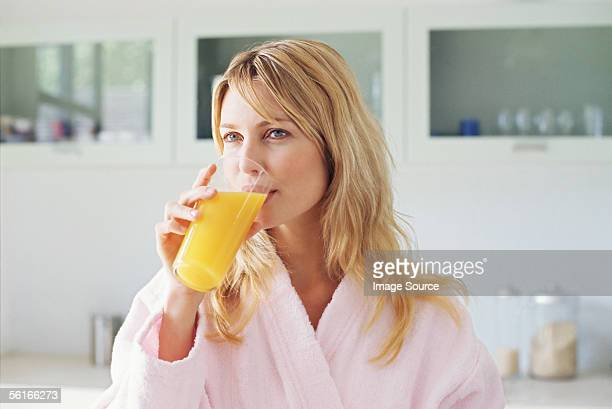woman drinking orange juice - orange juice stock pictures, royalty-free photos & images