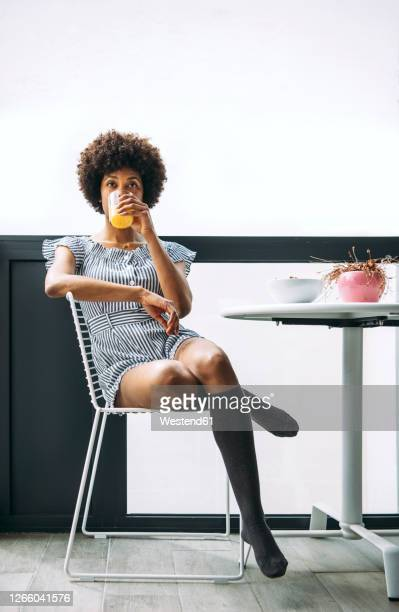 woman drinking orange juice while sitting on chair at balcony in penthouse - mini dress stock pictures, royalty-free photos & images
