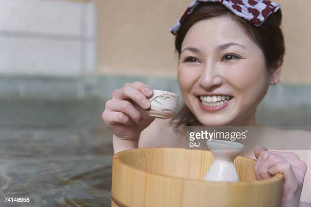 Woman drinking Sake in a hot tub, towel on her head, front view, Japan