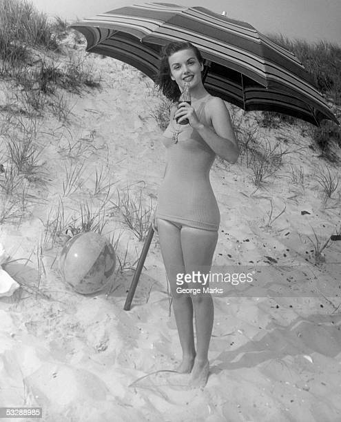 Woman drinking soda on beach