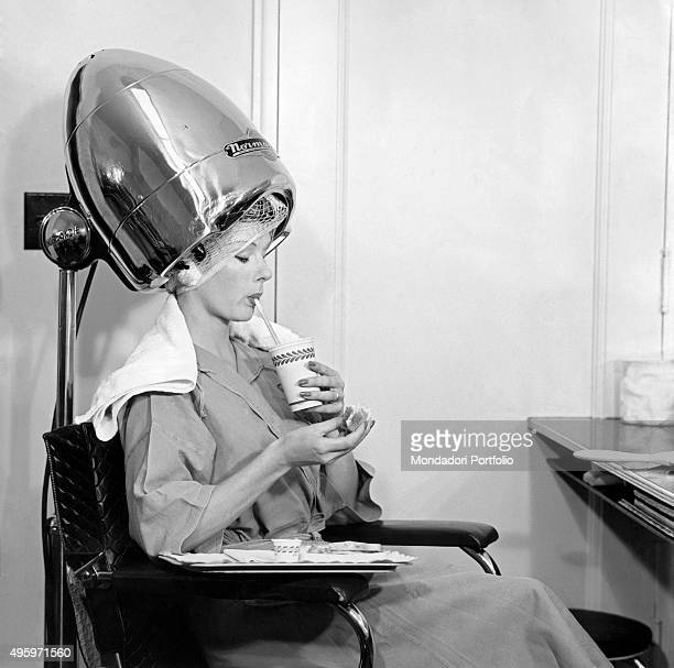 A woman drinking something under a hair drier 1960s