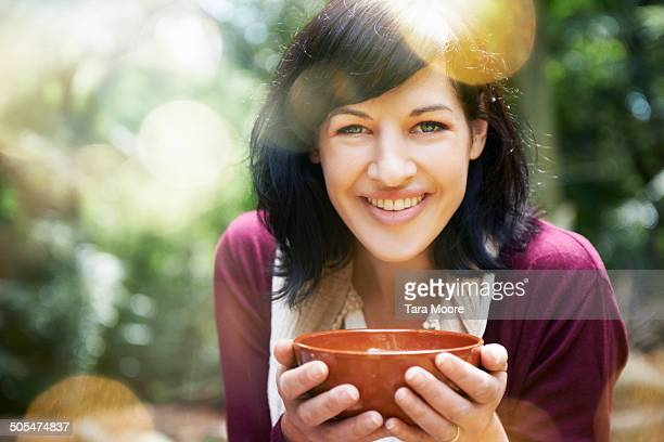 woman drinking soup in forest