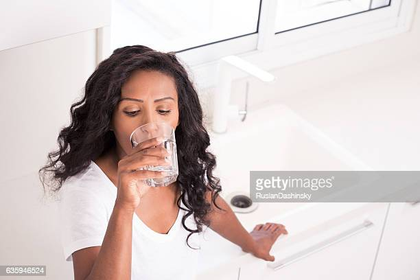 Woman drinking tap water.