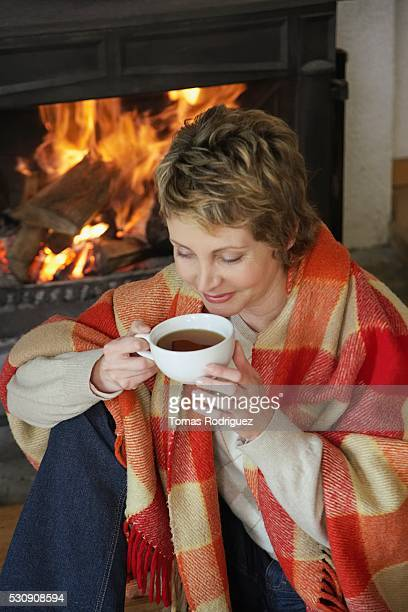 Woman drinking tea by fireplace