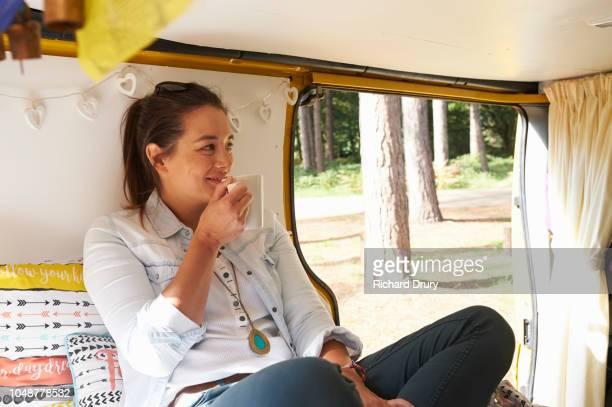 Woman drinking tea in her camper van