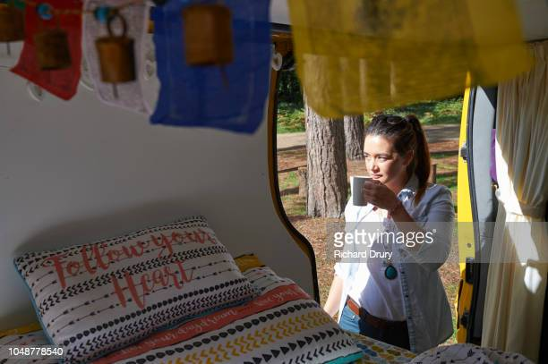 Woman drinking tea in the doorway of her camper van