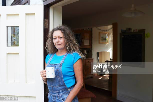 woman drinking tea in the doorway of her house - only mature women stock pictures, royalty-free photos & images
