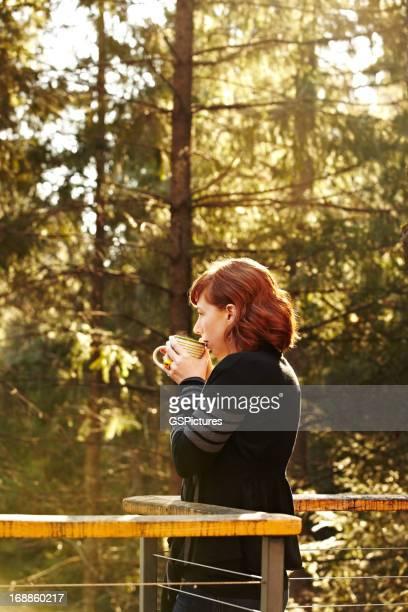 Mujer bebiendo té en la terraza en la naturaleza