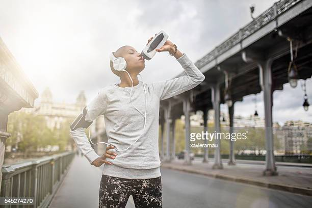 Woman drinking water after exercising in the streets of Paris