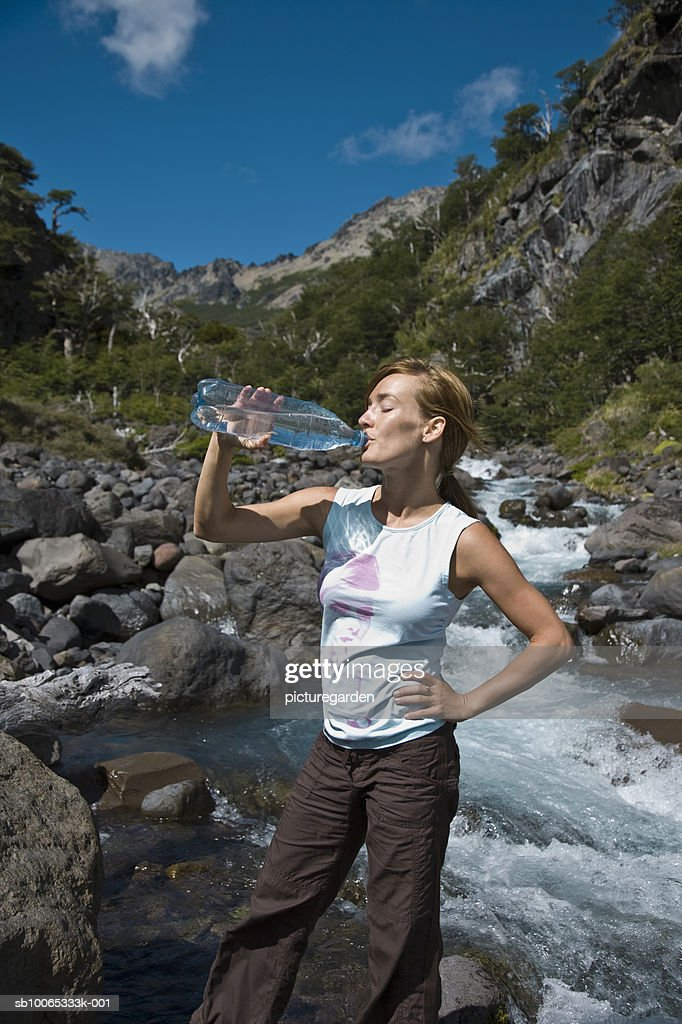 Woman drinking water by stream : Foto stock