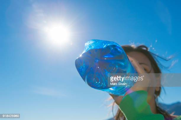 Woman Drinking Water from a Blue Bottle with Sunlight