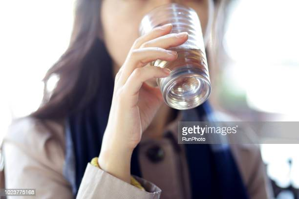 woman drinking water in cafe - trinkwasser stock-fotos und bilder