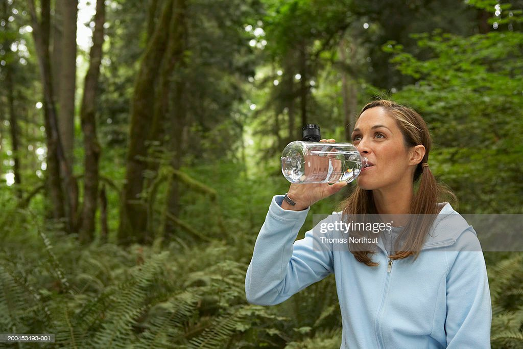 Woman drinking water in forest : Stock Photo