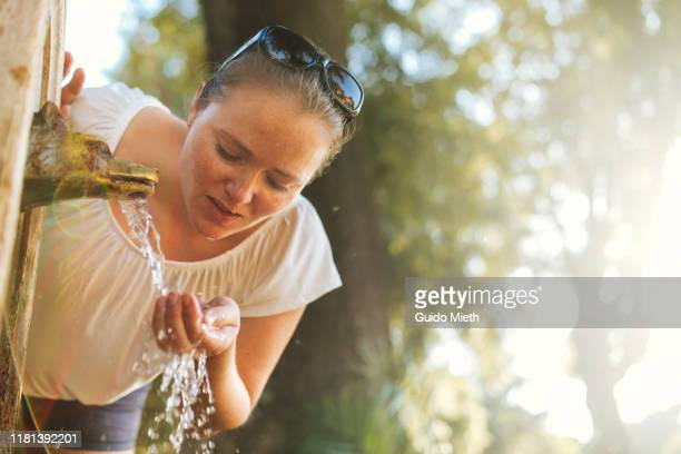 woman drinking water in rome from fountain. - femme fontaine photos et images de collection
