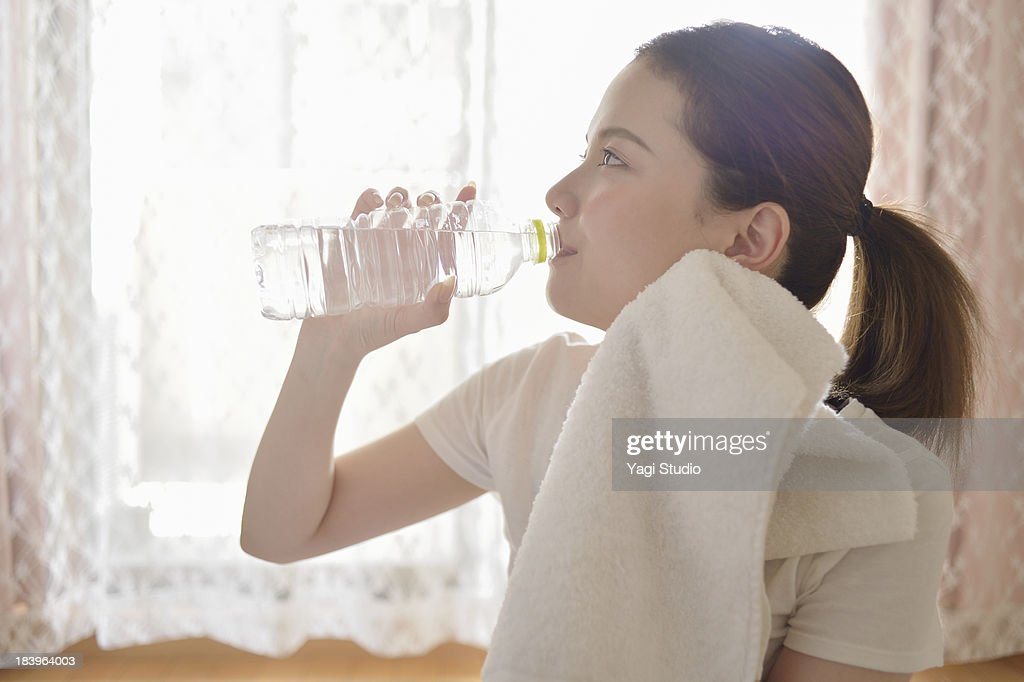 Woman drinking water in the room : Stock Photo