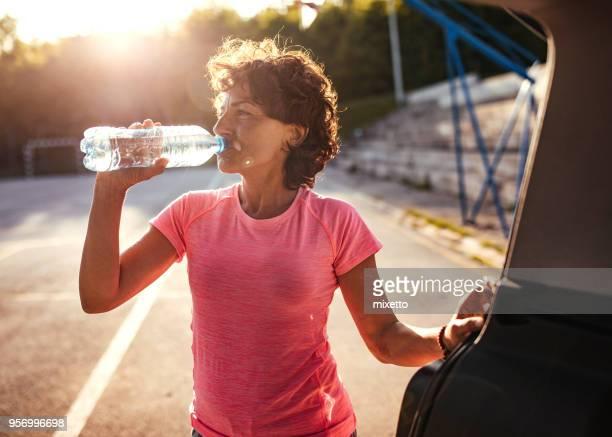 agua potable de mujer en la formación - agua potable fotografías e imágenes de stock