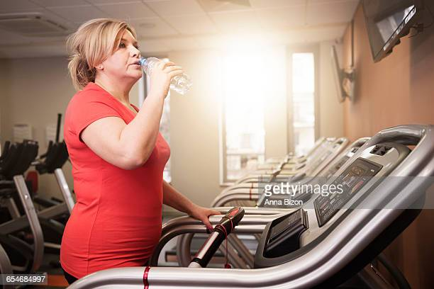 Woman drinking water while running at the gym. Debica, Poland