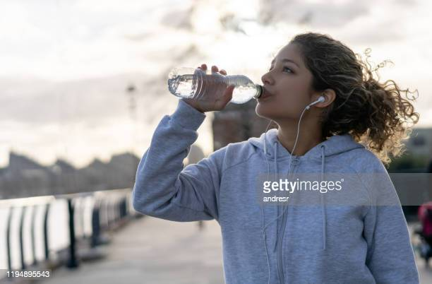 woman drinking water while running outdoors - drink stock pictures, royalty-free photos & images