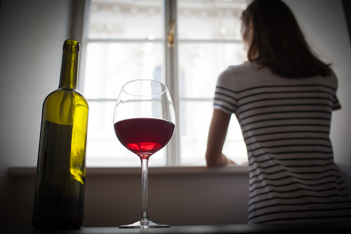 Woman drinking wine alone in the dark room 916253032