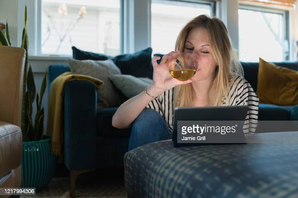 woman drinking wine and looking at tablet at home - happy hour stock pictures, royalty-free photos & images