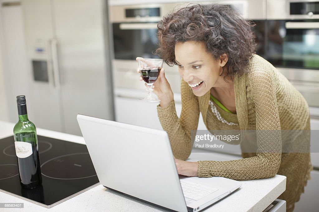 Woman drinking wine and using laptop at home : Stock Photo