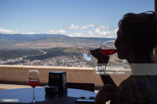 woman drinking wine at table against landscape - 国 ジョージア ストックフォトと画像