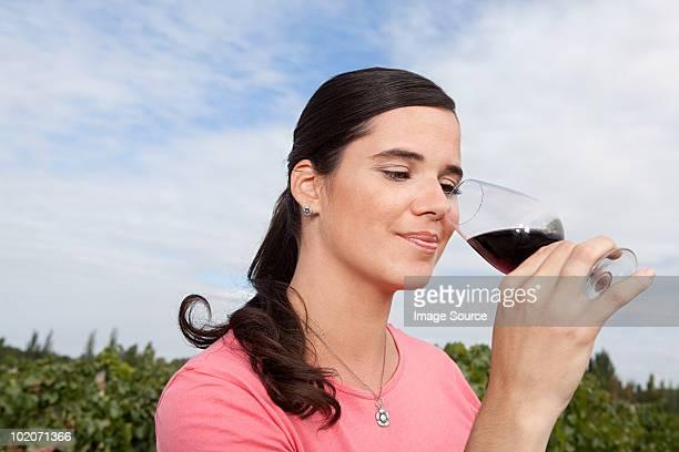 Woman drinking wine in vineyard