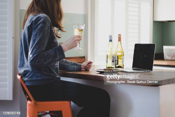 woman drinking wine, looking at the laptop, making video conference - drink stock pictures, royalty-free photos & images