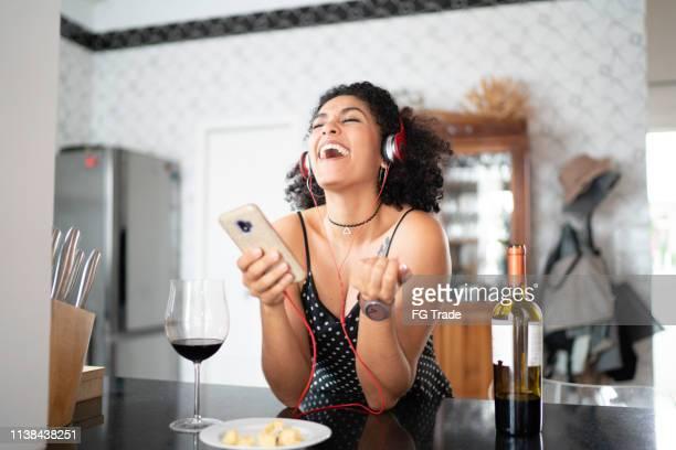 vinho bebendo da mulher ao escutar seu favorito no telefone esperto - música - fotografias e filmes do acervo