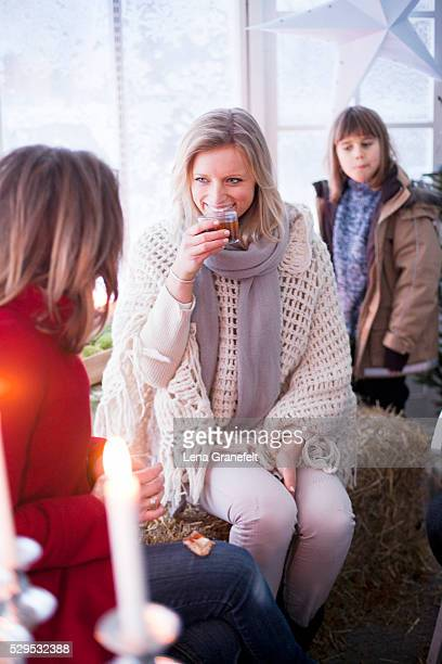 Woman drinking with two girls in winter clothes in greenhouse