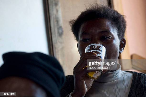 A woman drinks a beer in a 'shebeen' an illegal tavern usually in someone's home in Gugulethu on February 10 about 15Km from the centre of Cape Town...