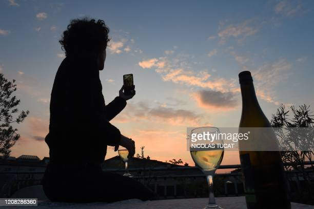 A woman drinks a glass of wine as she speaks and shares a drink with friends via a video call on March 26 in Bordeaux southwestern France in the...