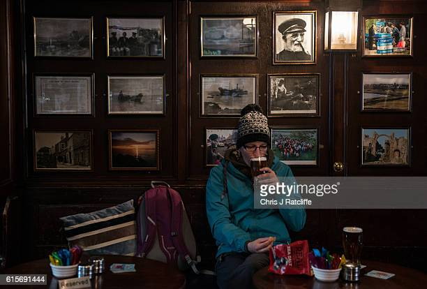A woman drinks a pint of beer in The Shipp Inn on the Holy Island of Lindisfarne Northumberland The Holy Island of Lindisfarne is a tidal island off...