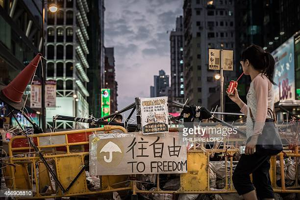 A woman drinks a soda as she walks past a barricade erected by prodemocracy demonstrators in Hong Kong on October 9 2014 Hong Kong's government...