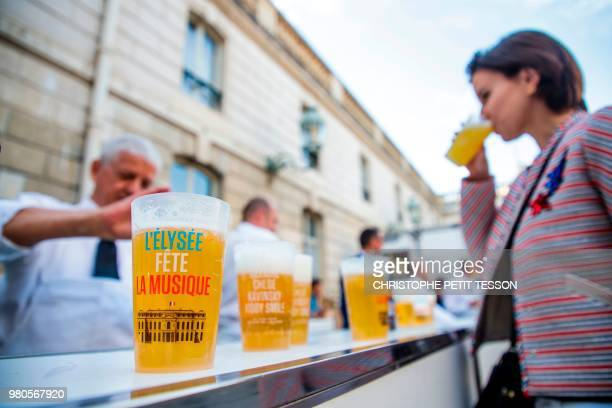 A woman drinks an alcoholfree beer during the annual 'Fete de la Musique' in the courtyard of the Elysee Palace in Paris on June 21 2018