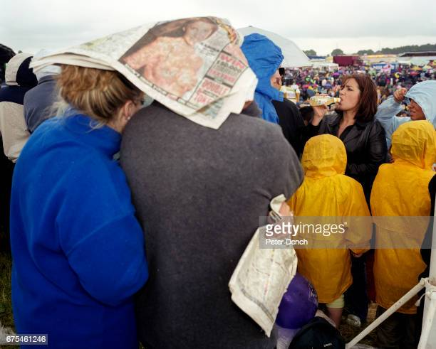 A woman drinks an alcopop and a couple try to shelter from the rain under a copy of the Sun newspaper on Derby Day at Epsom Downs Racecourse June 2001